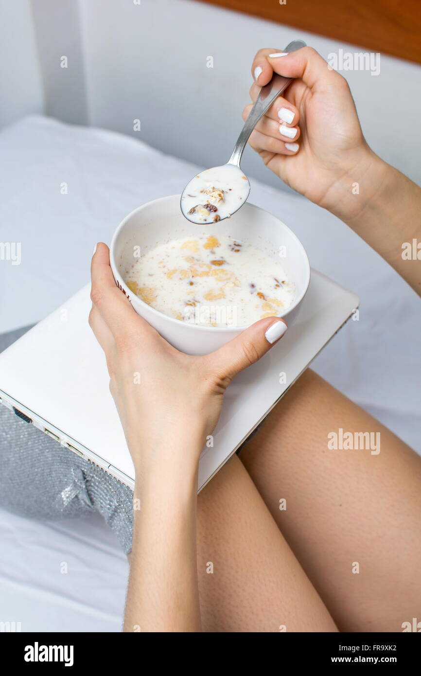 Girl eating cereals for breakfast  in bed - Stock Image