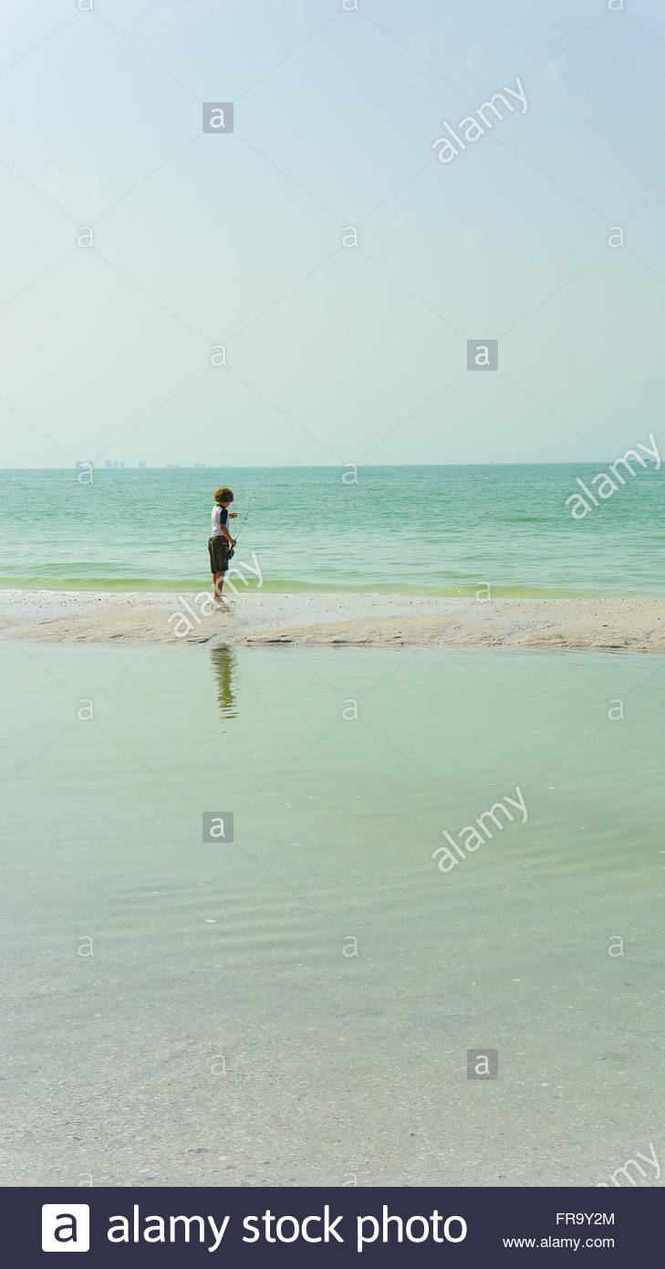 Young boy with his fishing rod. He is fishing on Sanibel Island, Florida, in the Gulf of Mexico. At low tide, shallow - Stock Image