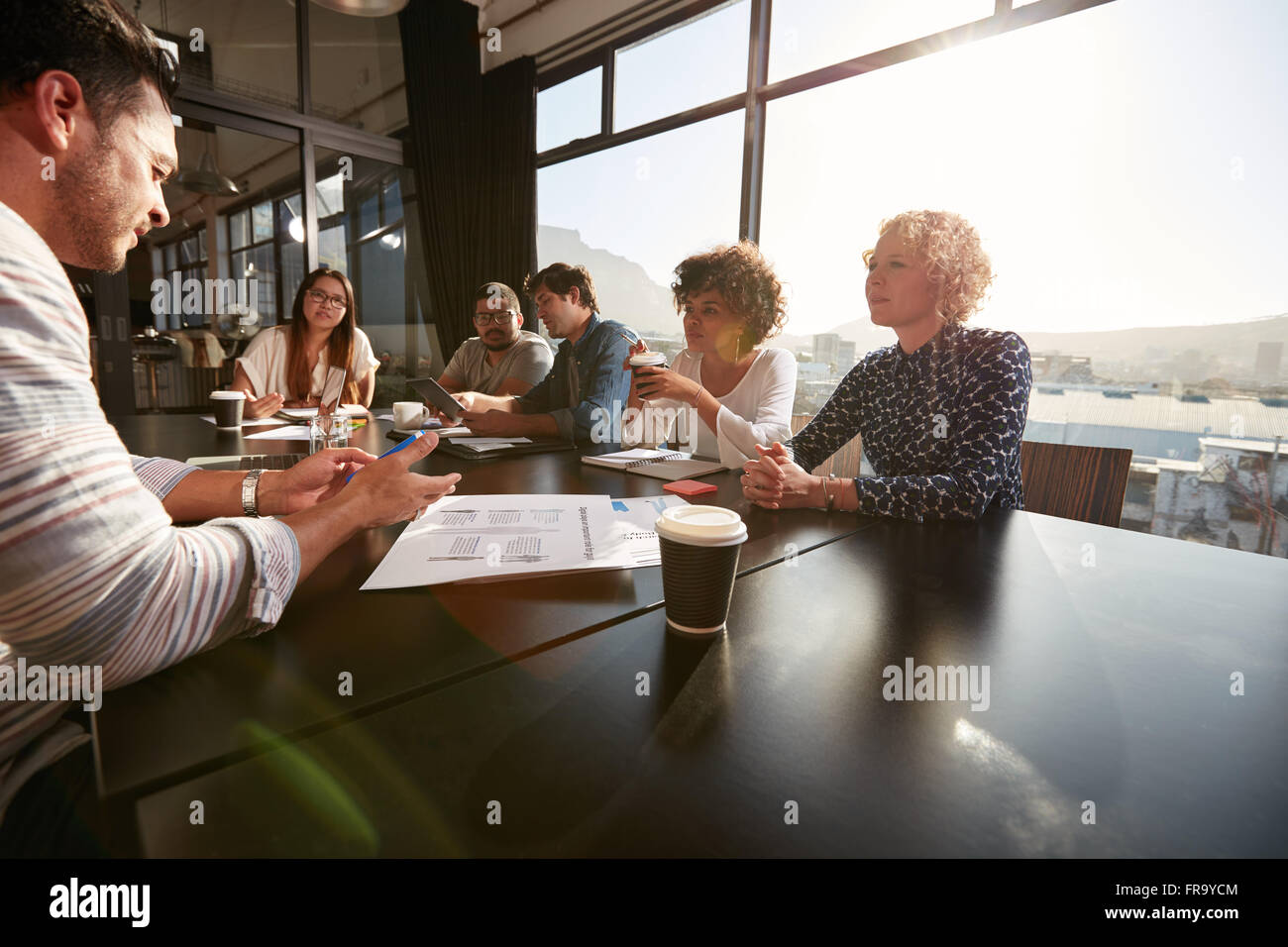 Portrait of creative team sitting around a table discussing new project plans. Mixed race people meeting in office. - Stock Image
