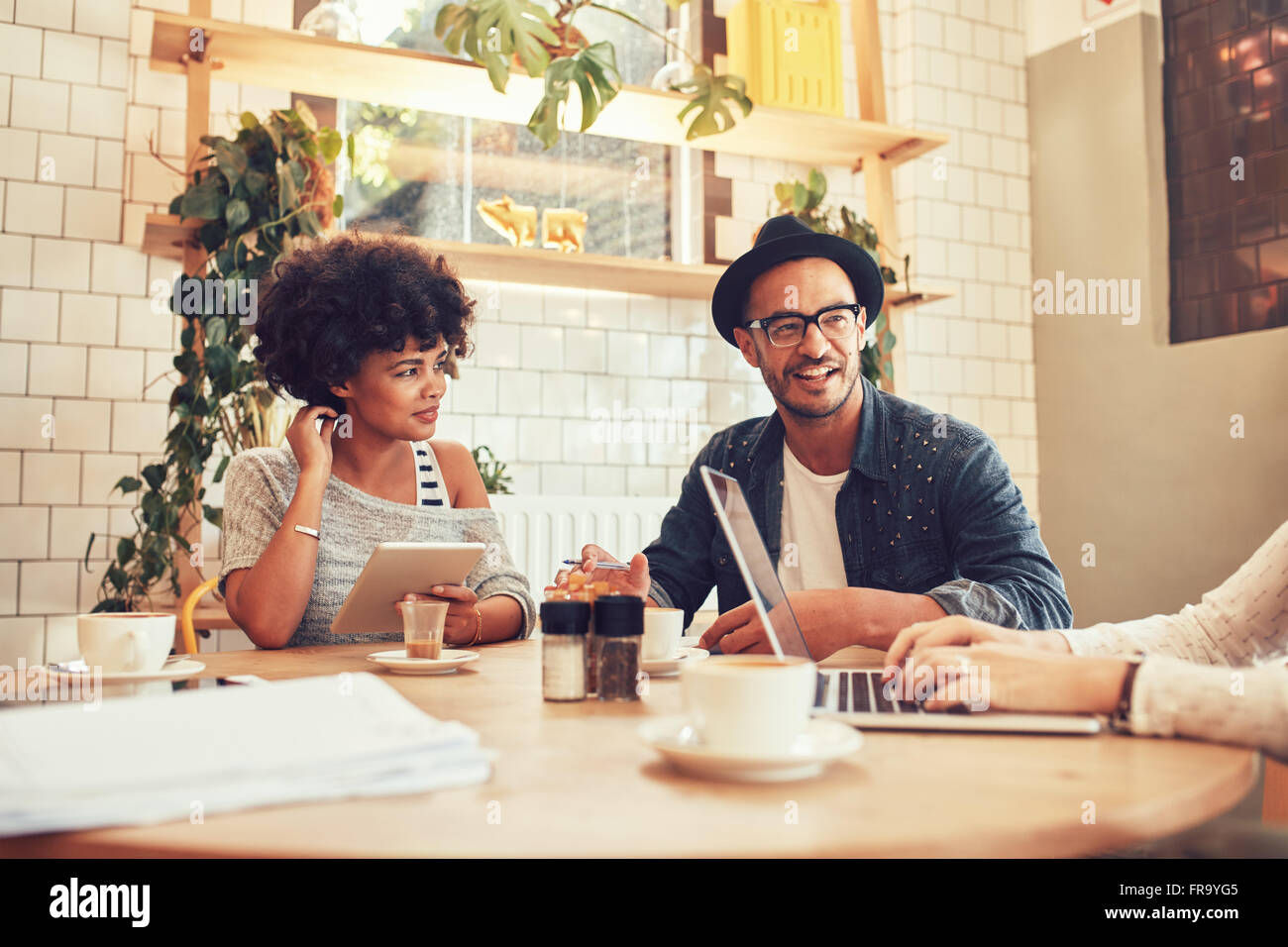 Portrait of happy young people sitting at a cafe with laptop and digital tablet. Group of friends sitting together - Stock Image