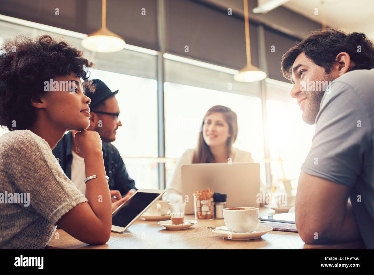 Portrait of group of young people sitting at a cafe and discussing work. Young men and women at coffee shop for - Stock Image