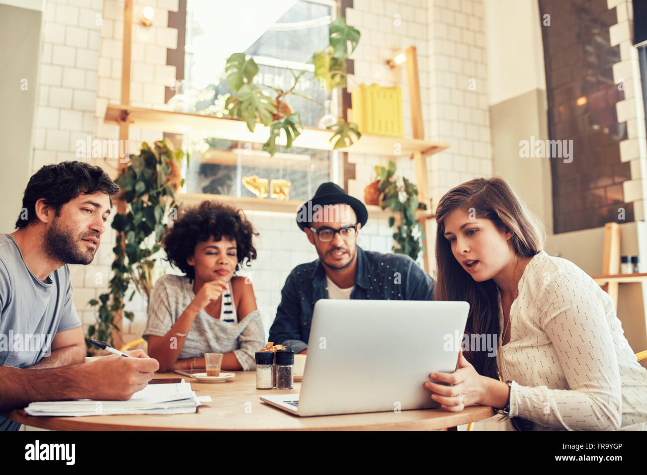 Portrait of young creative team sitting at a cafe and looking at a laptop. Young woman giving business presentation - Stock Image