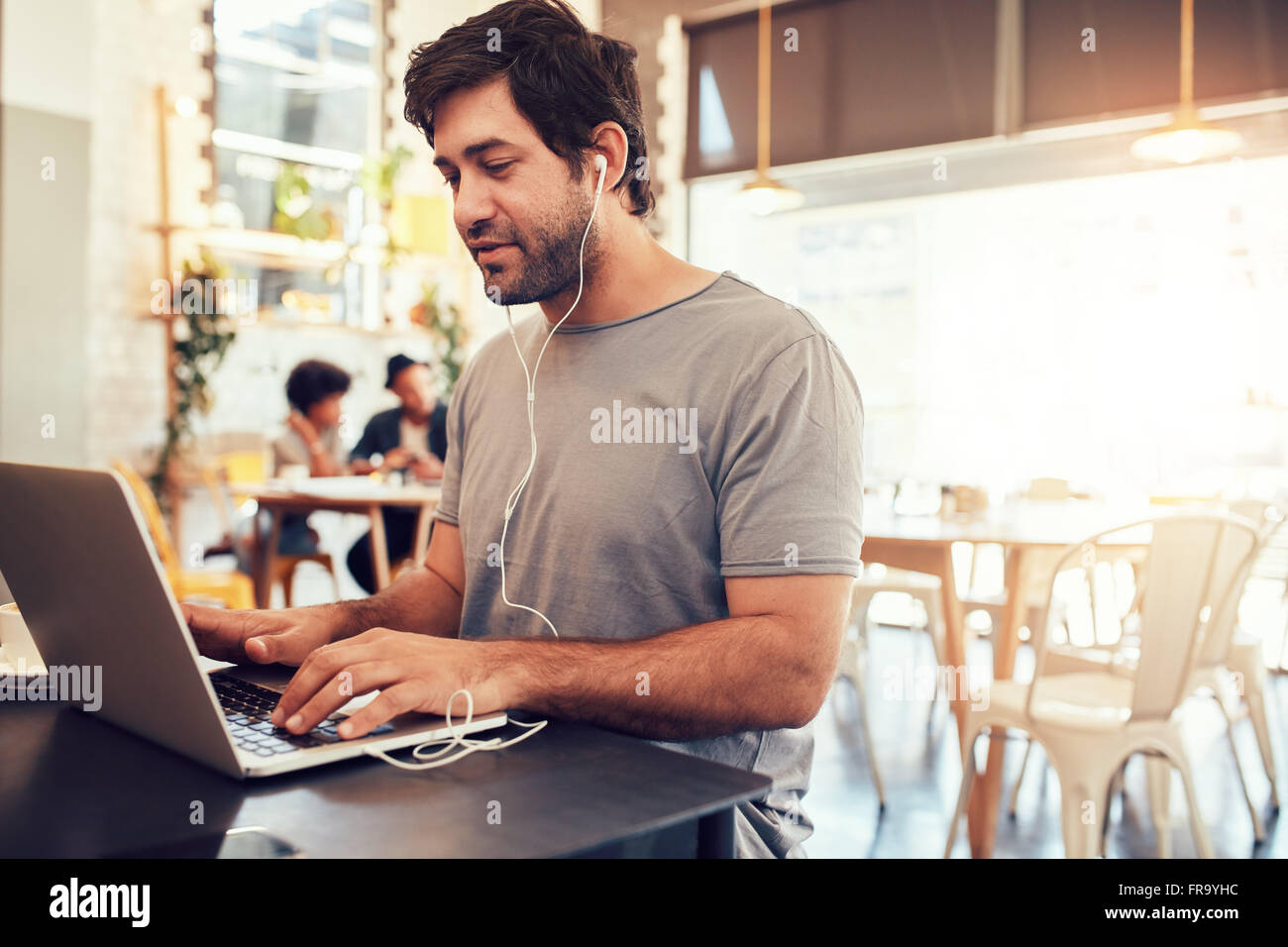 Portrait of handsome young man with earphones working on laptop while sitting at a coffee shop. Young guy at a cafe - Stock Image