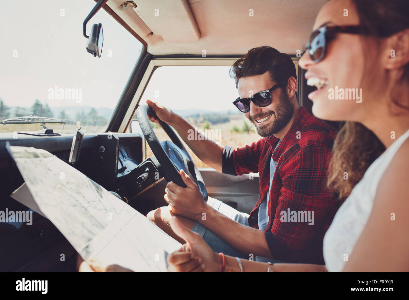Happy young couple with a map in the car. Smiling man and woman using map on roadtrip. Stock Photo