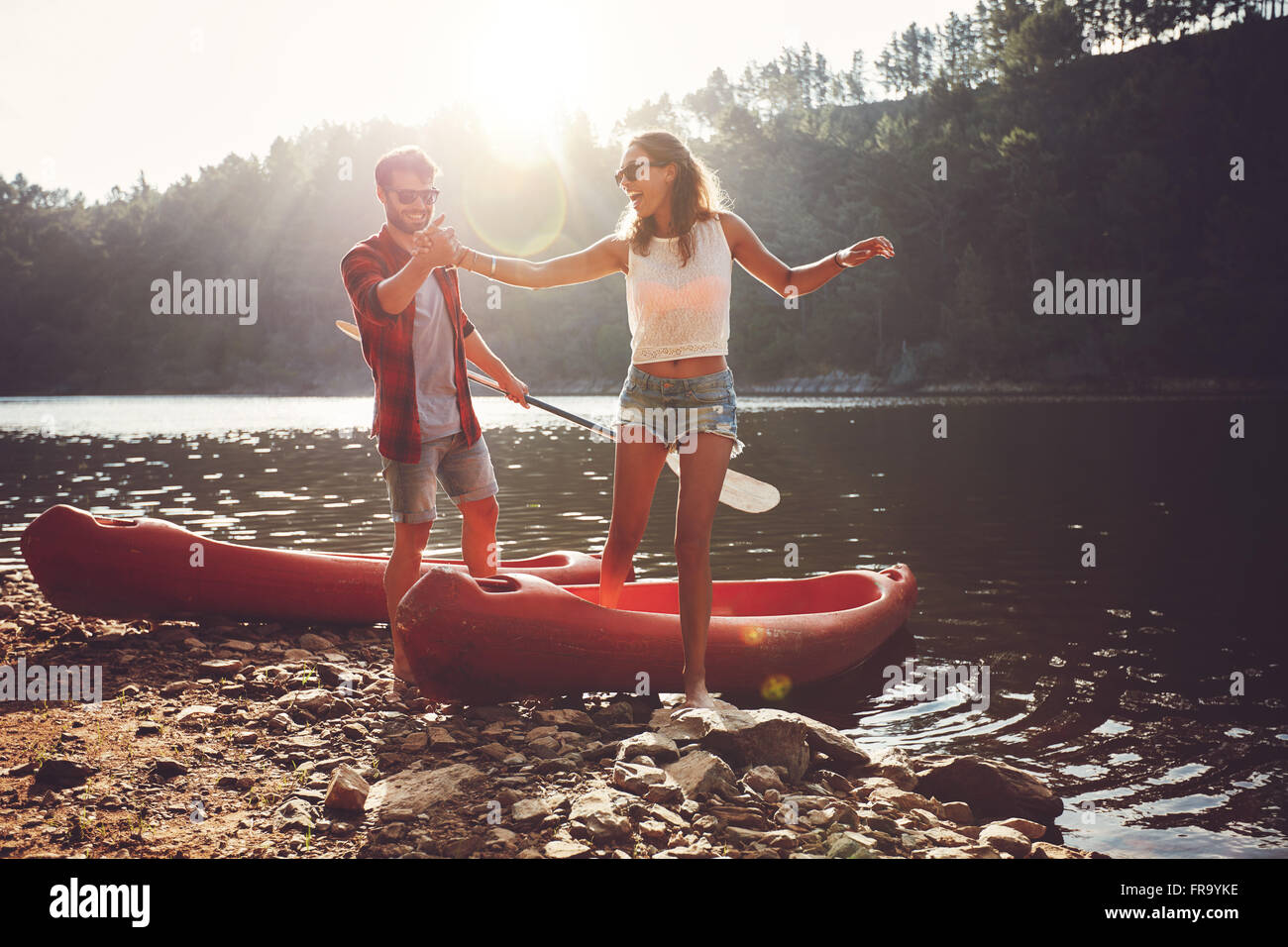 Young man helping woman to step out of a kayak. Couple after kayaking in the lake on a sunny day. - Stock Image