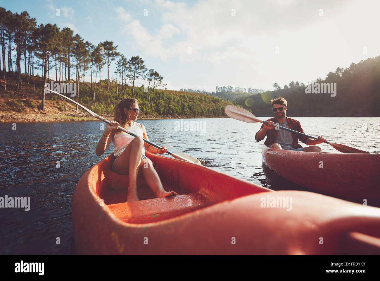 Young couple kayaking on a lake. Young kayakers rowing on lake on summer day. - Stock Image
