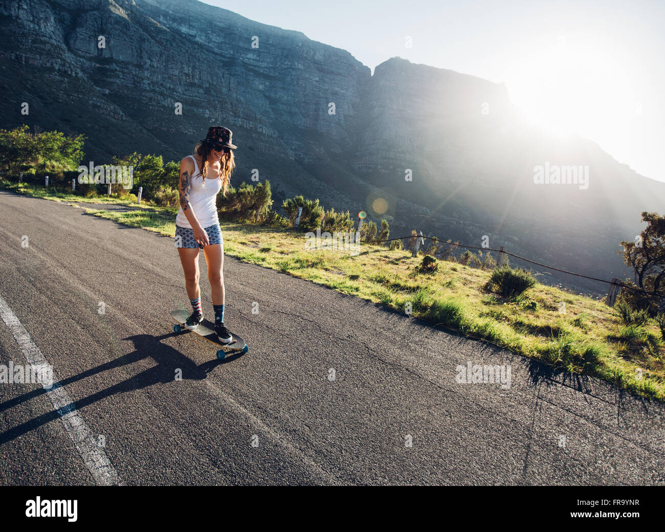 Young woman skating outdoors on rural road. Female longboarding on a summer day. - Stock Image