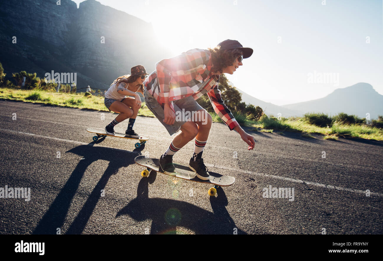 Side portrait of young people skateboarding together on road. Young man and woman longboarding down the road on - Stock Image