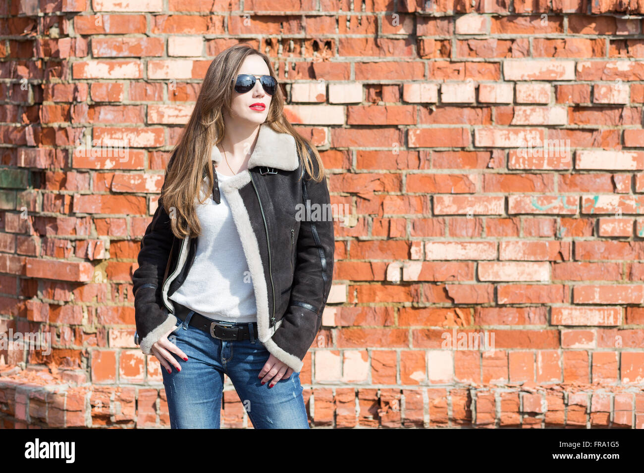 Pretty european girl in sunglasses with photo camera against red brick wall. Happy young woman at sunny day - Stock Image