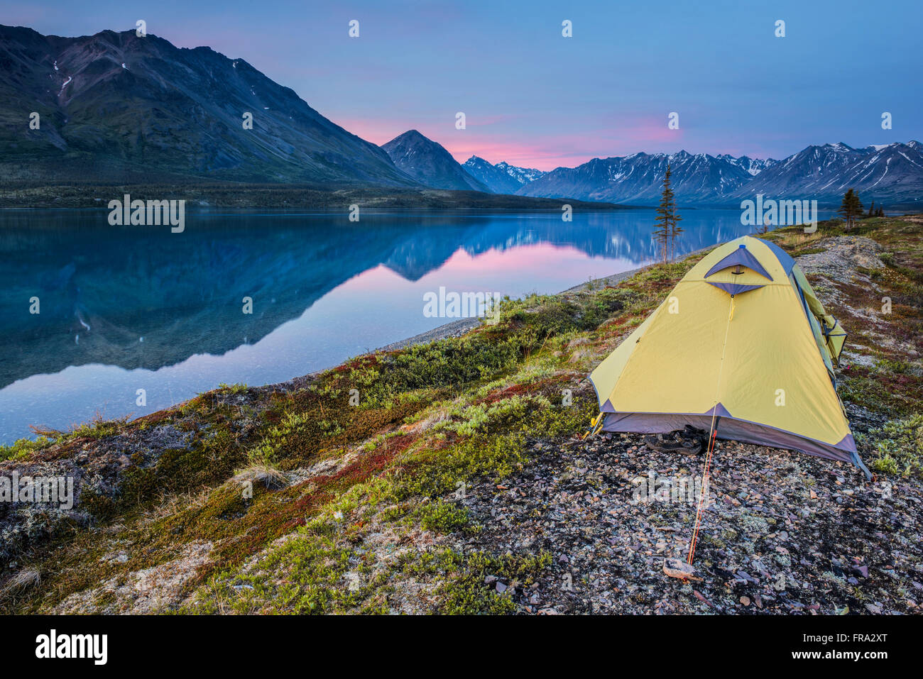 Scenic view of Lower Twin Lake with a backpacking tent in the foreground and sunset, Lake Clark National Park & - Stock Image