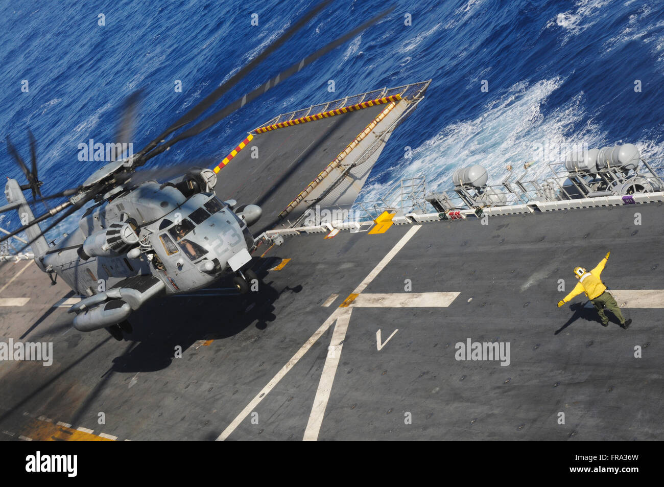 A crewman onboard the USS Peleliu (LHA-5) guides a CH-53 Sea Stallion helicopter in for a landing; Hawaii, USA - Stock Image