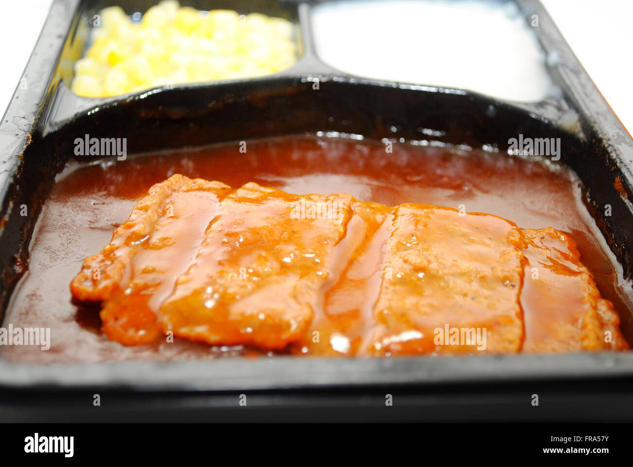 TV Dinner with Focus on a BBQ Boneless Pork Patty Stock Photo