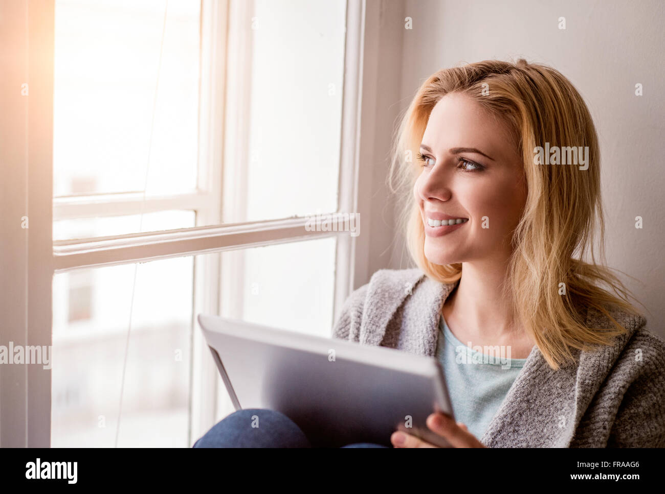 Woman with tablet sitting on window sill, sunny day - Stock Image