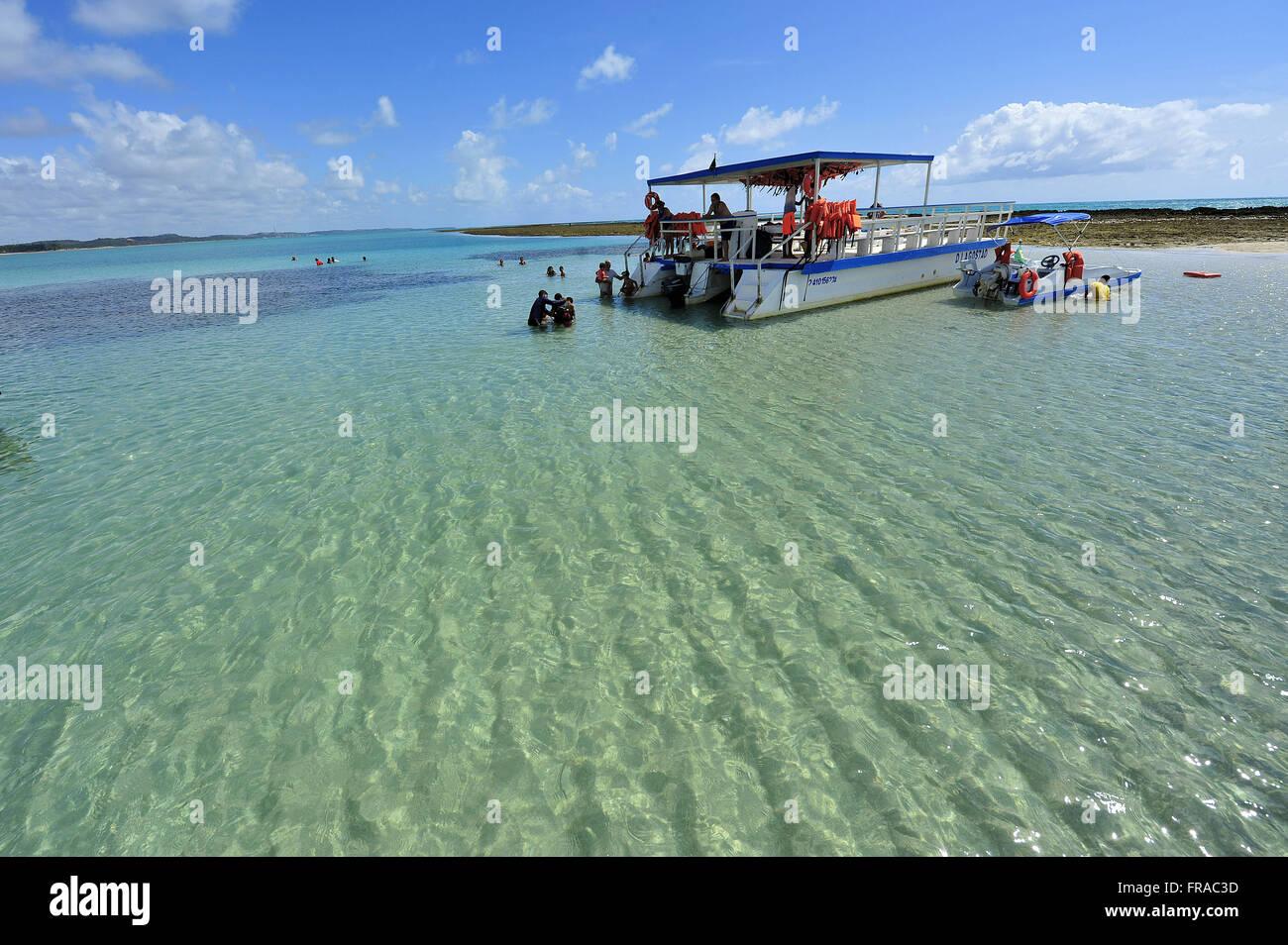Turistas em barco de passeio na Praia de Japaratinga - Stock Image