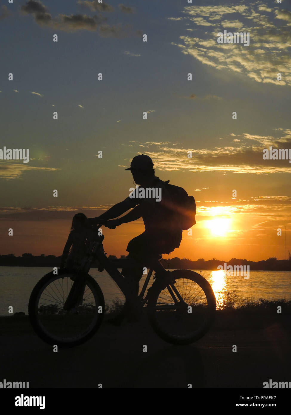 Cyclist watches the sunset on the shore of Lake Guaiba downtown - Stock Image
