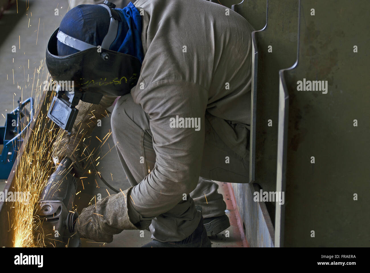 Laborer with sander in shipbuilding - Stock Image
