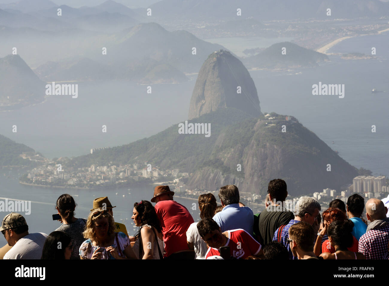 Tourists observing and photographing the Complex Sugar Loaf from Corcovado lookout - Stock Image