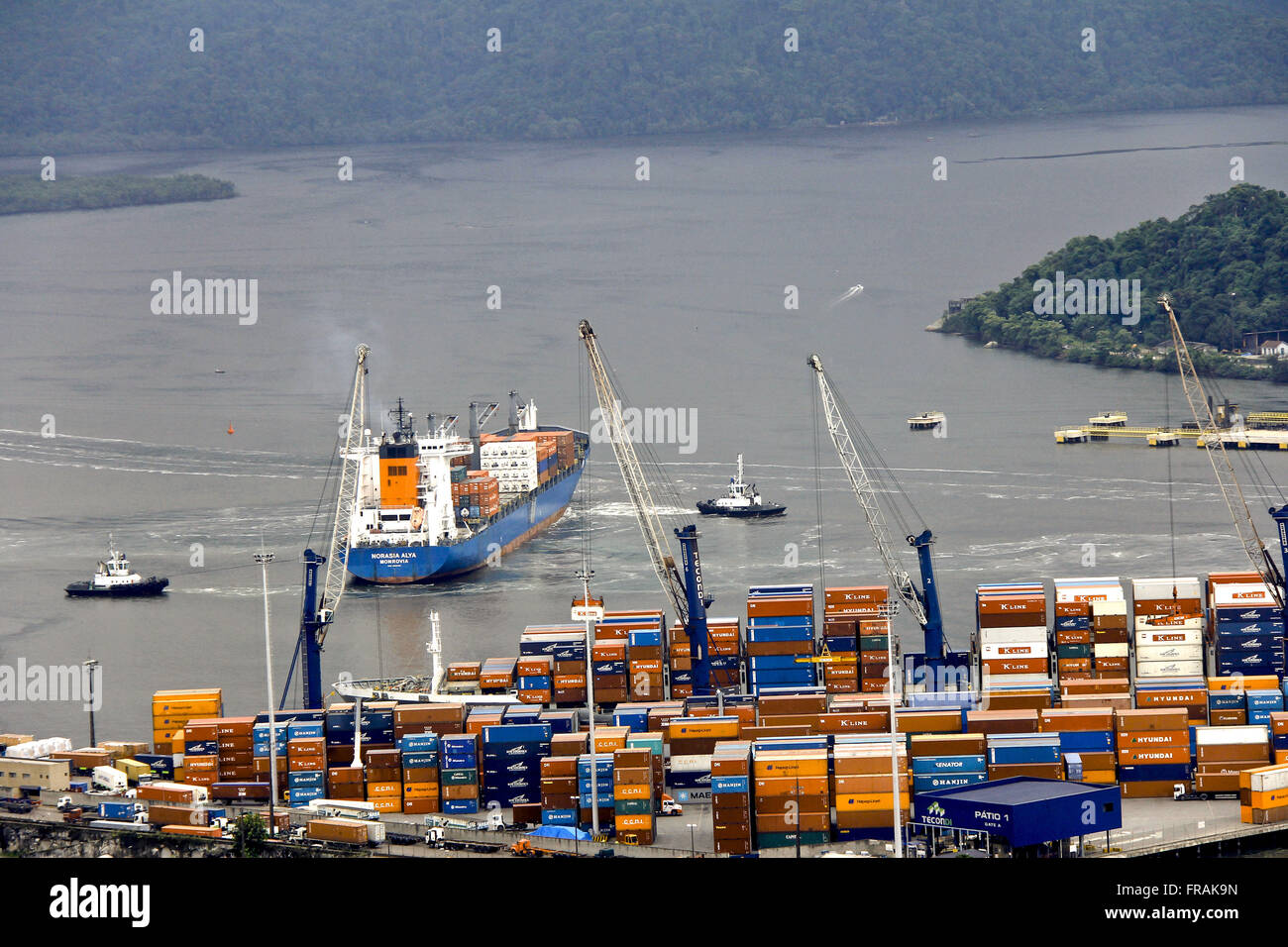 Port of Santos - tugs guiding movement of containers on ship terminal - Stock Image