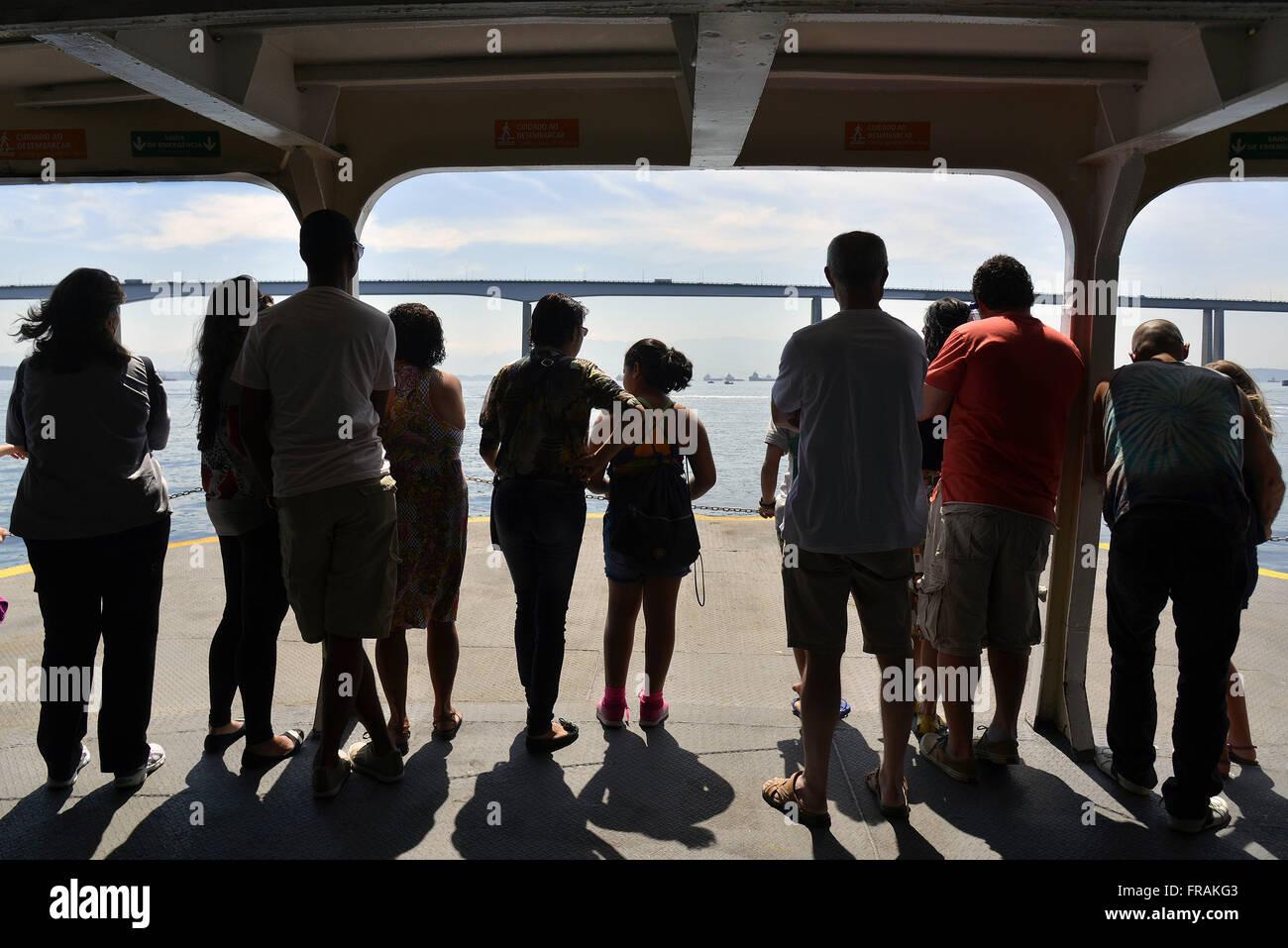 Passengers observing the Rio-Niteroi Bridge Boat ride in Guanabara Bay - Stock Image