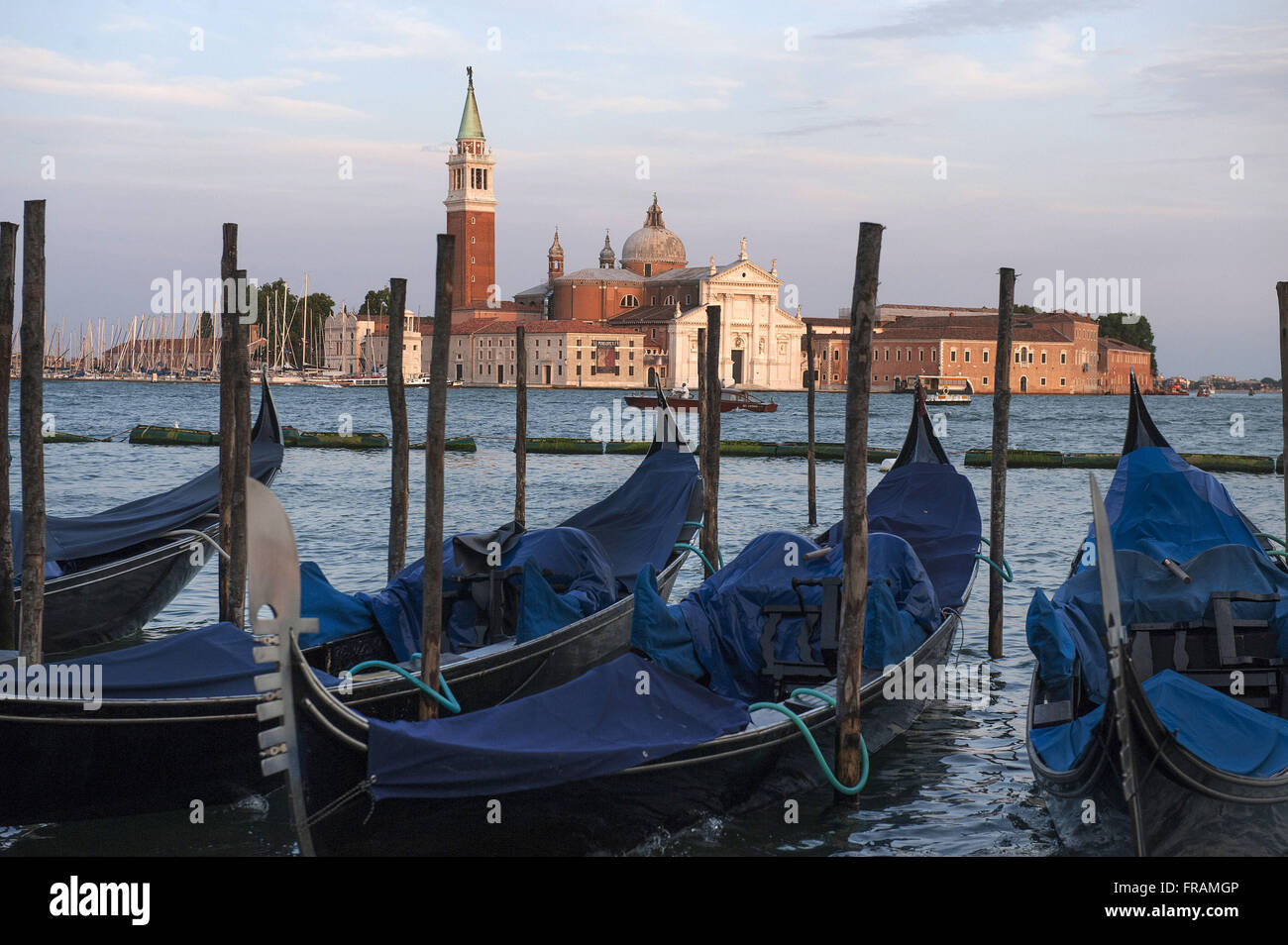 Gondolas anchored in pier of Venice Lagoon - Incidental Belfry and Church of San Giorgio Maggiore - Stock Image