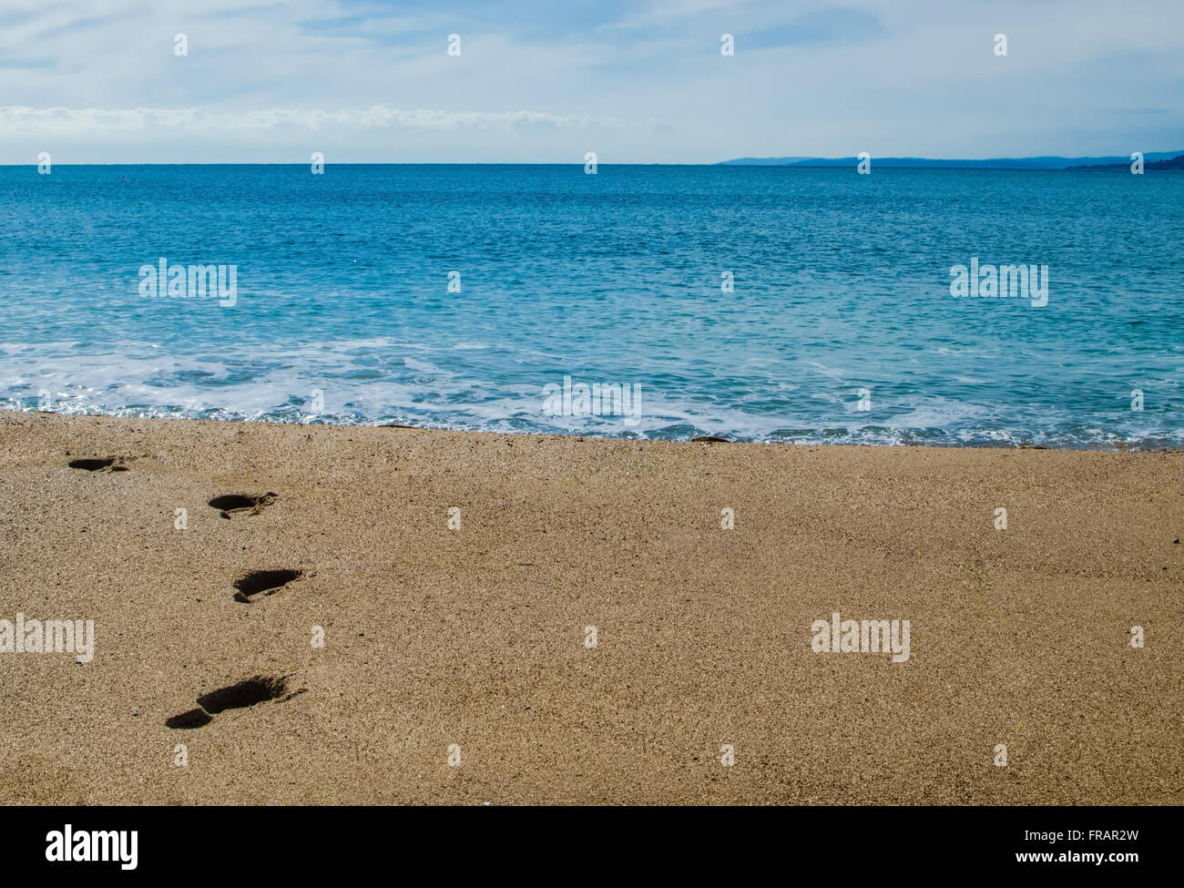 Footprints on the beach - Stock Image
