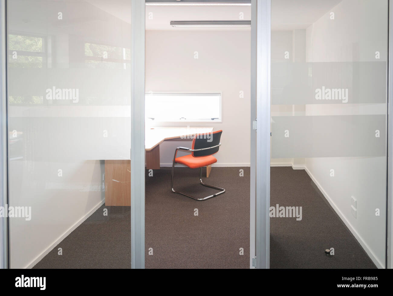 Small vacant business office with desk and chair, Christchurch, Canterbury Region, New Zealand - Stock Image