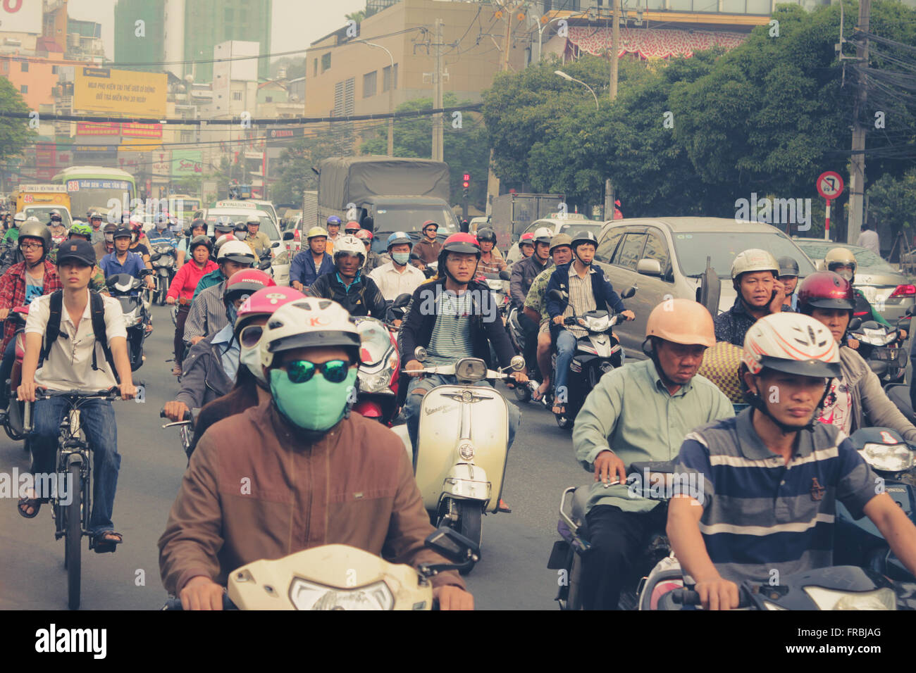 Saigon, Vietnam, January 17. 2014: Road traffic crowded with motorbikes and scooter drivers. - Stock Image