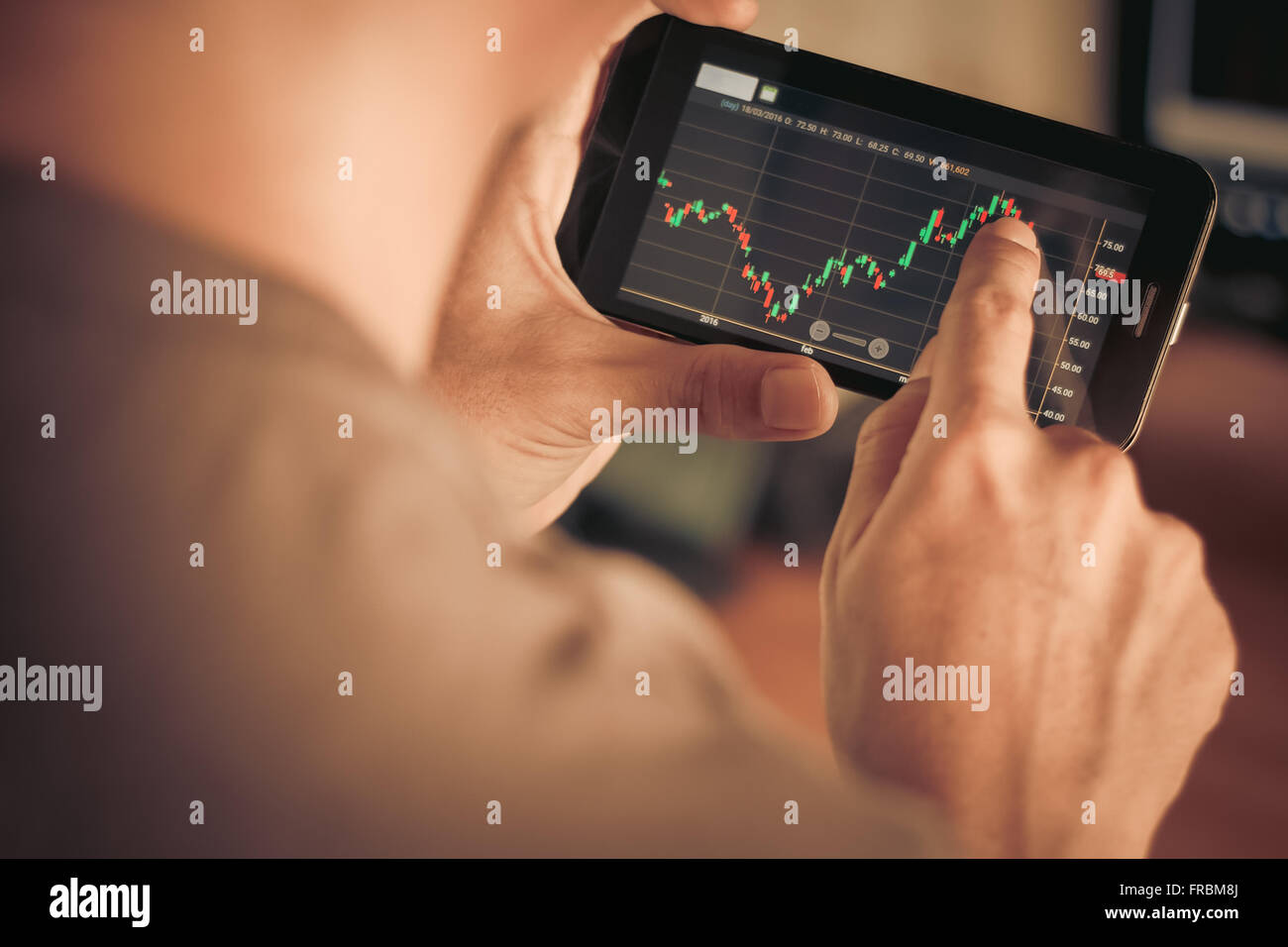 a man checking stock market on smartphone - Stock Image