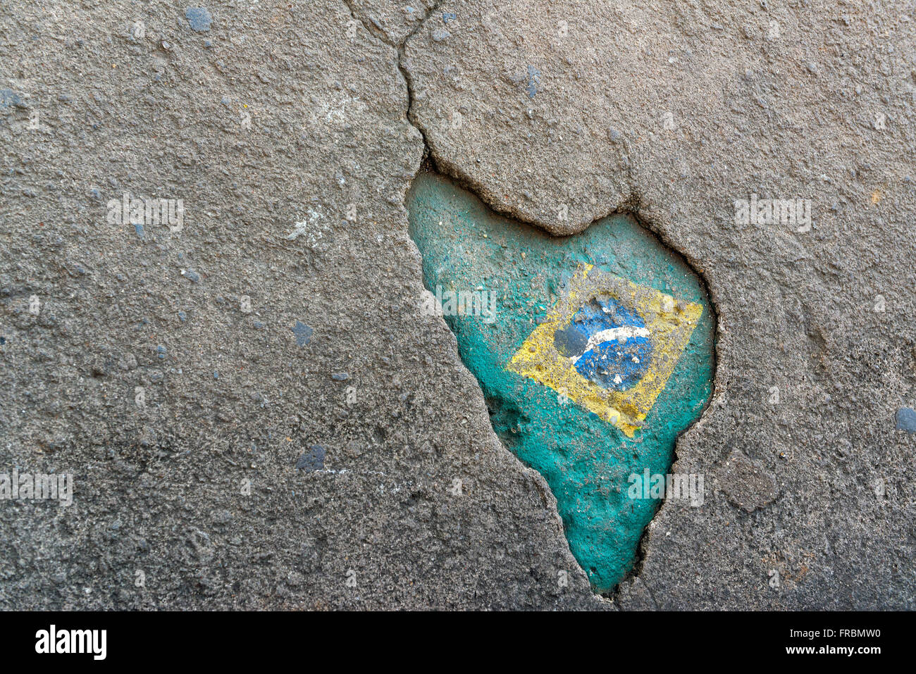 Hole in the sidewalk with design that resembles the map of Brazil - Stock Image