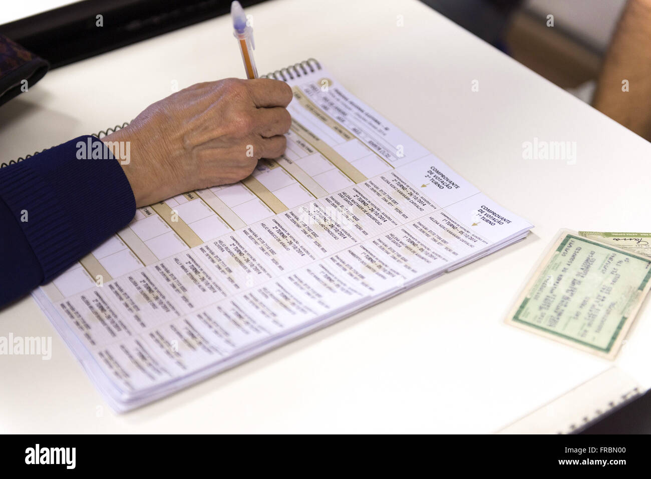 Voter signs contract vote by the board member before voting on the electronic ballot box - Stock Image