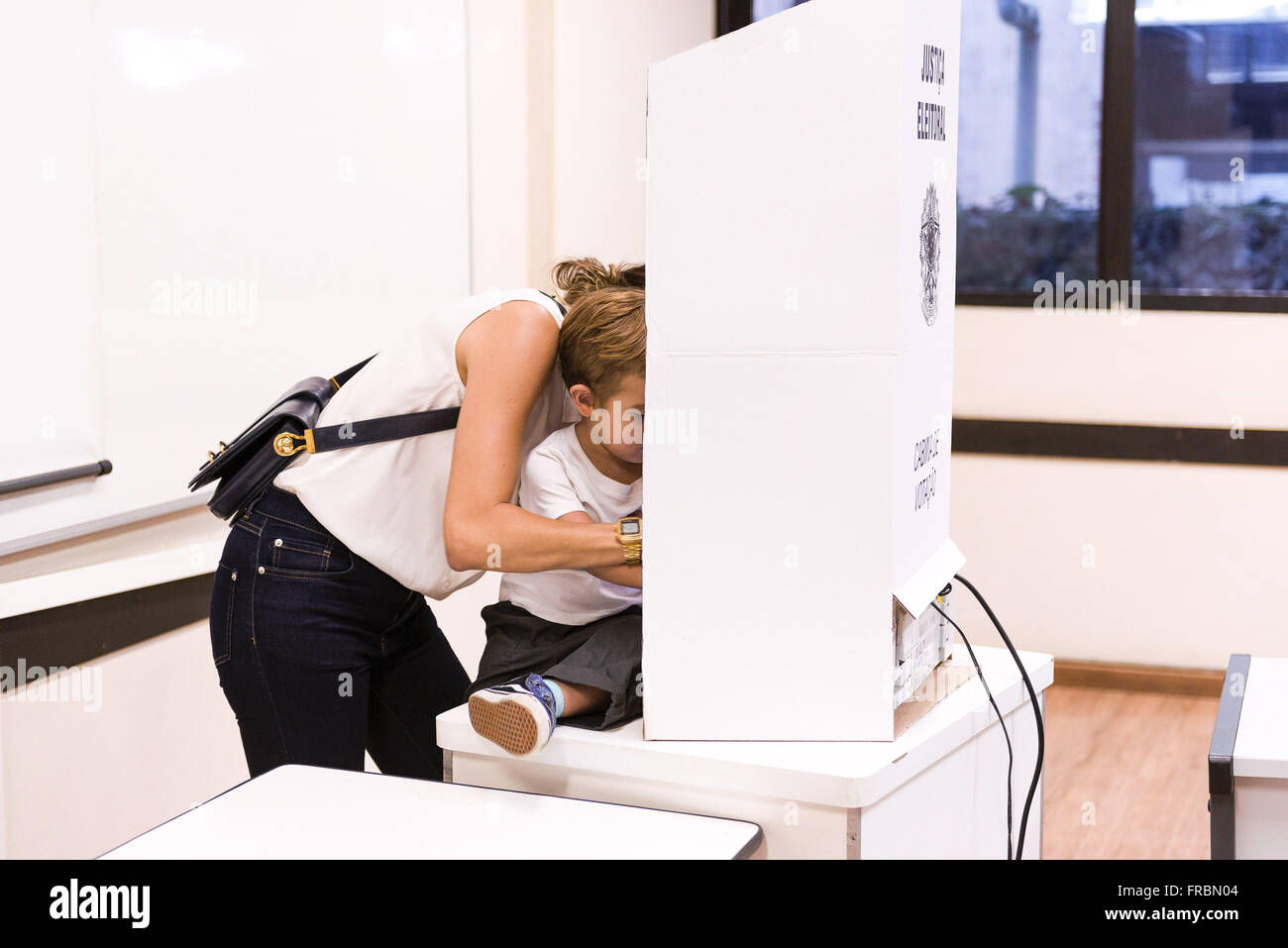Mother and son in electronic voting urn at PUC-Rio - Elections 2014 - Stock Image