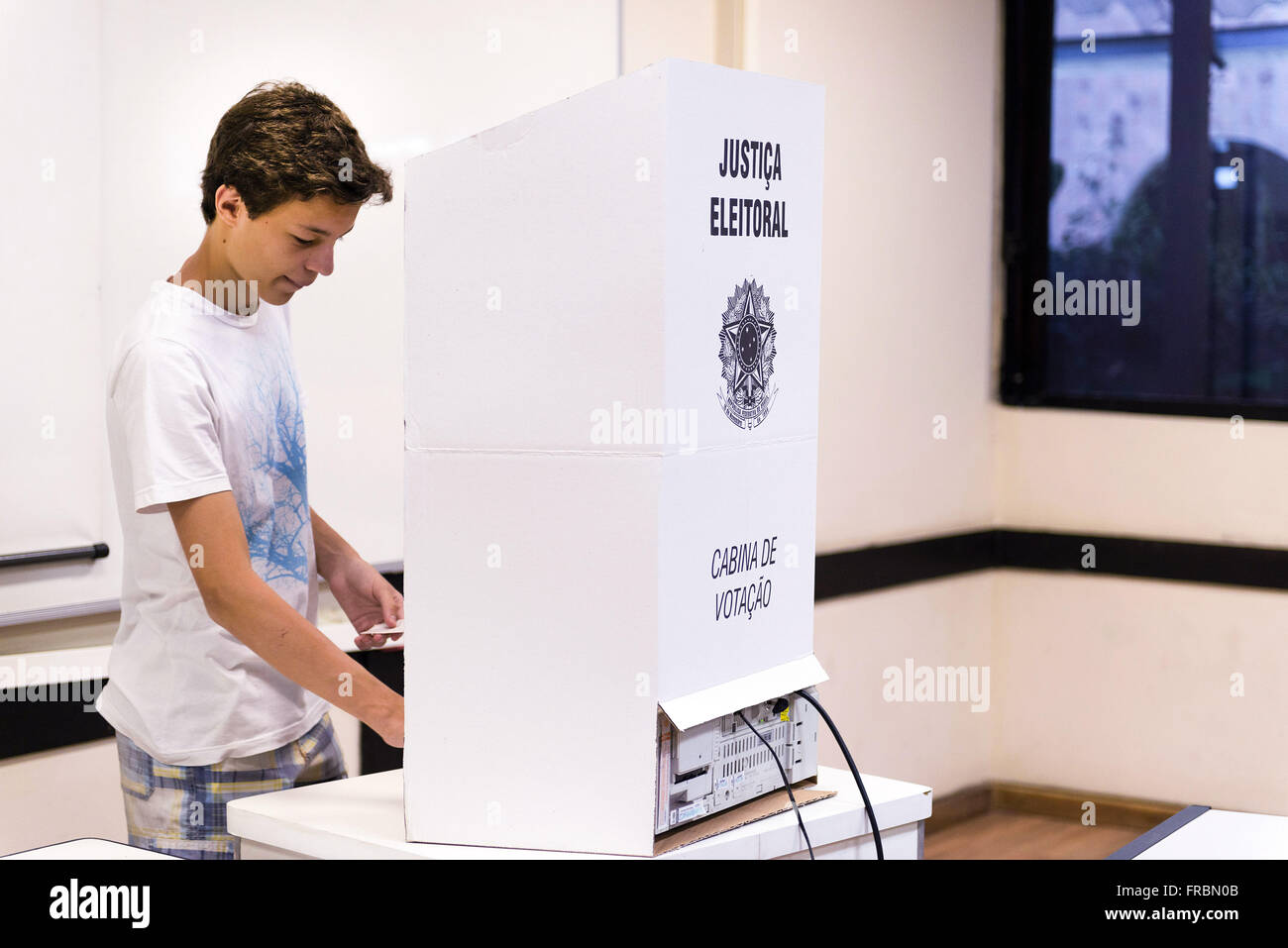 Teen voter voting in electronic urn at PUC-Rio - Elections 2014 - Stock Image