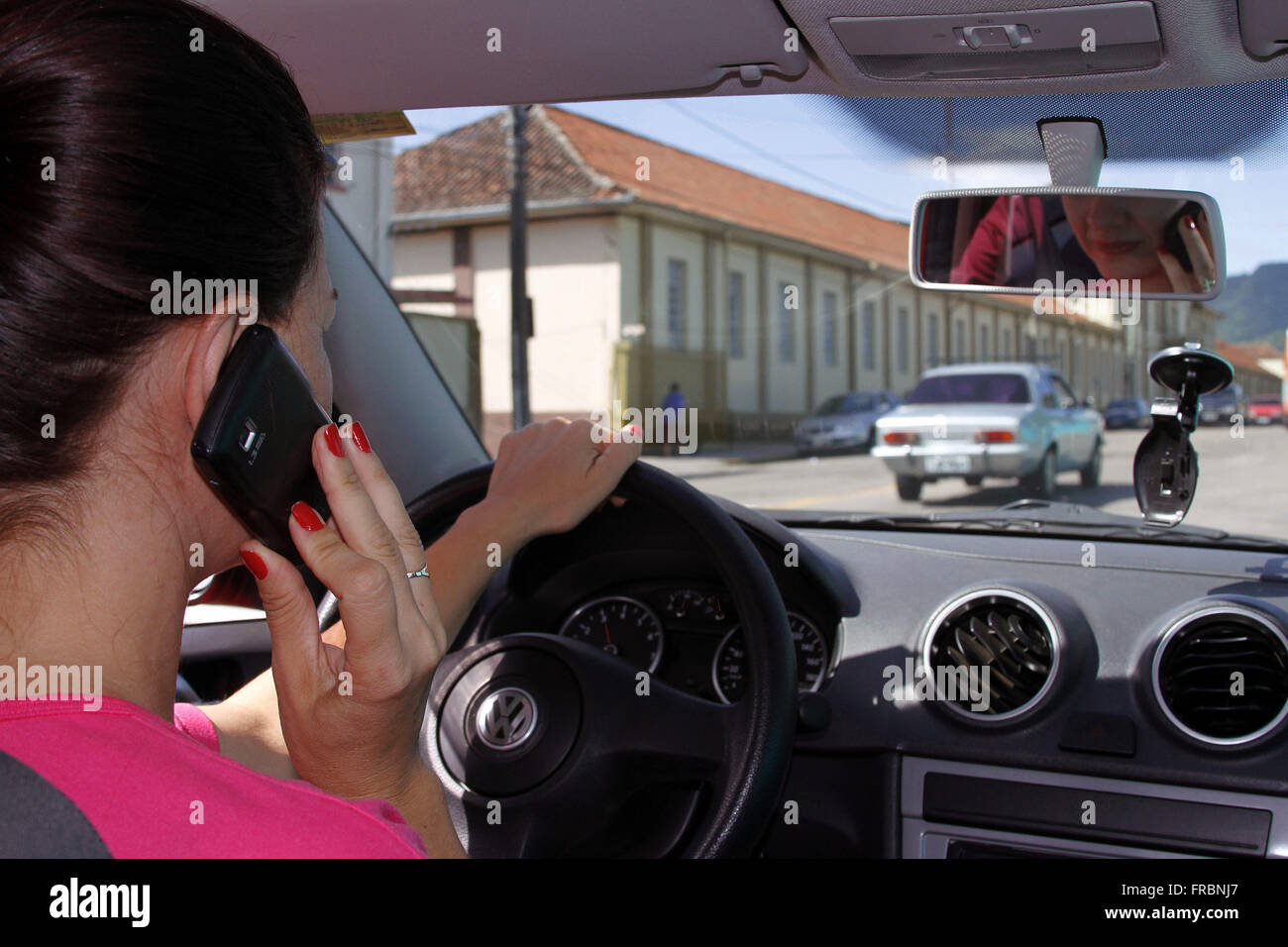 Driver using mobile phone while driving automobile - Stock Image