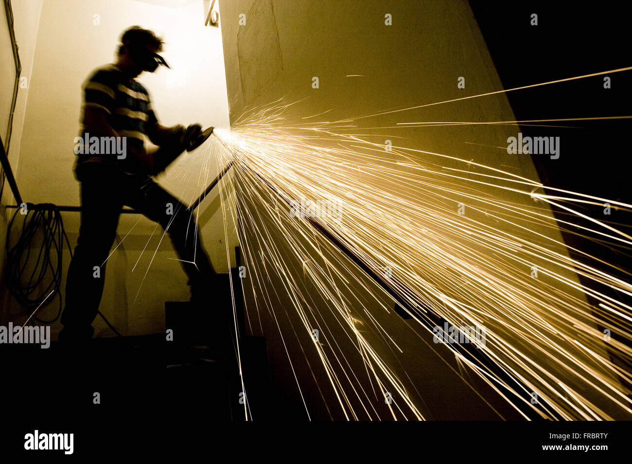 Workman using emery to fix handrail stair residential building - Stock Image