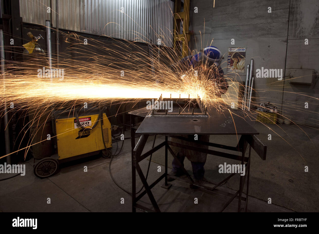 Workman with emery sanding of steel plate - manufactures high voltage transformers - Stock Image