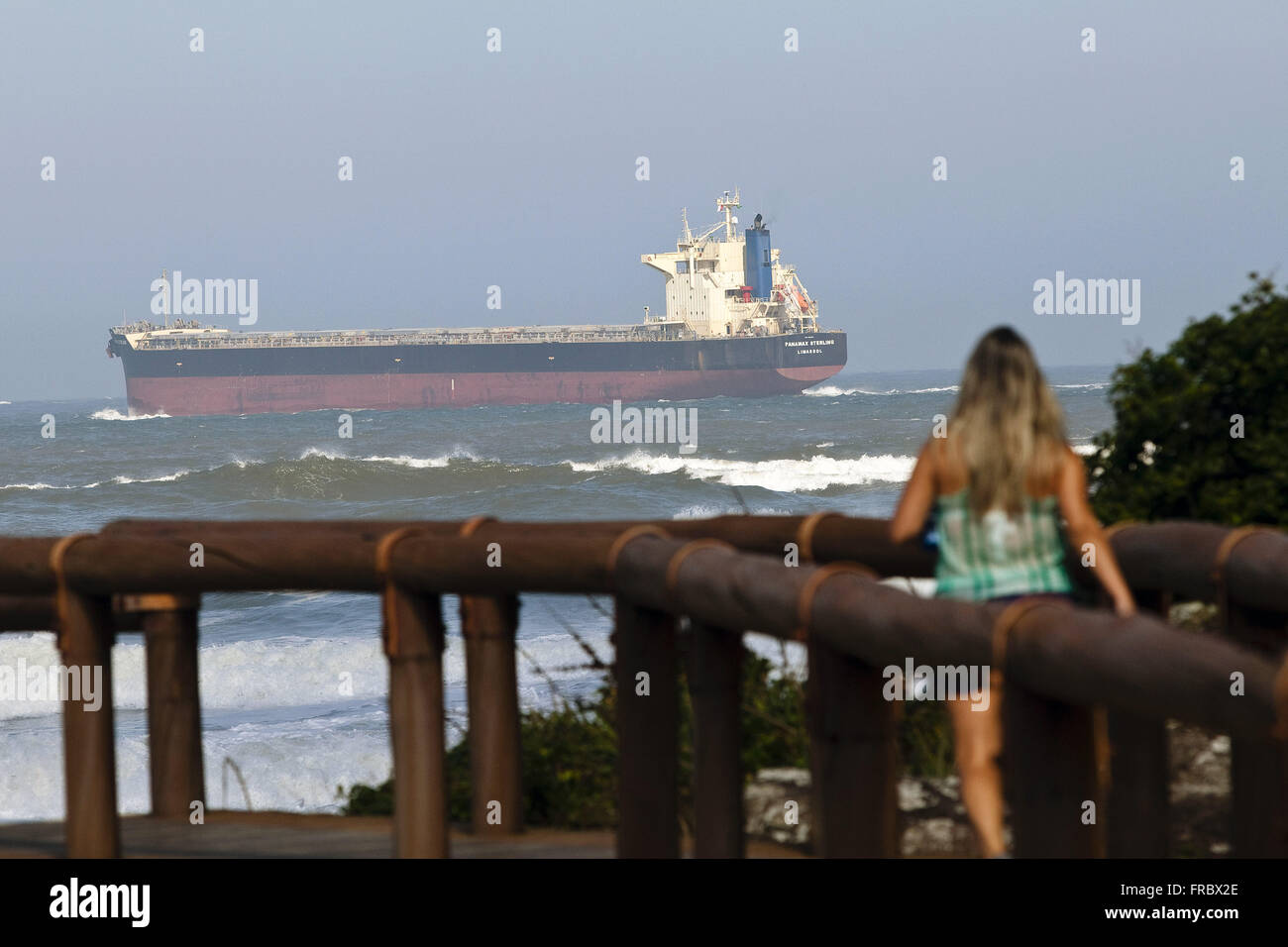 Tourist on wood pier and the bottom vessel approaching the Bay of Paranagua in Ilha do Mel - Stock Image