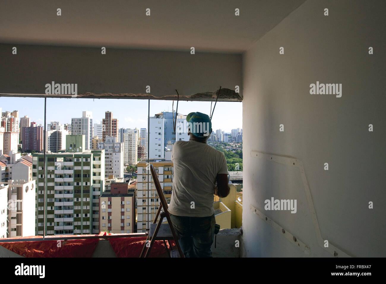 Mason exchanging apartment window - Stock Image