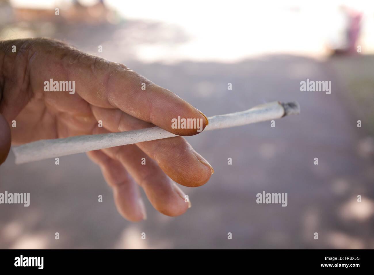 Elderly crafted cigarette smoking - Stock Image