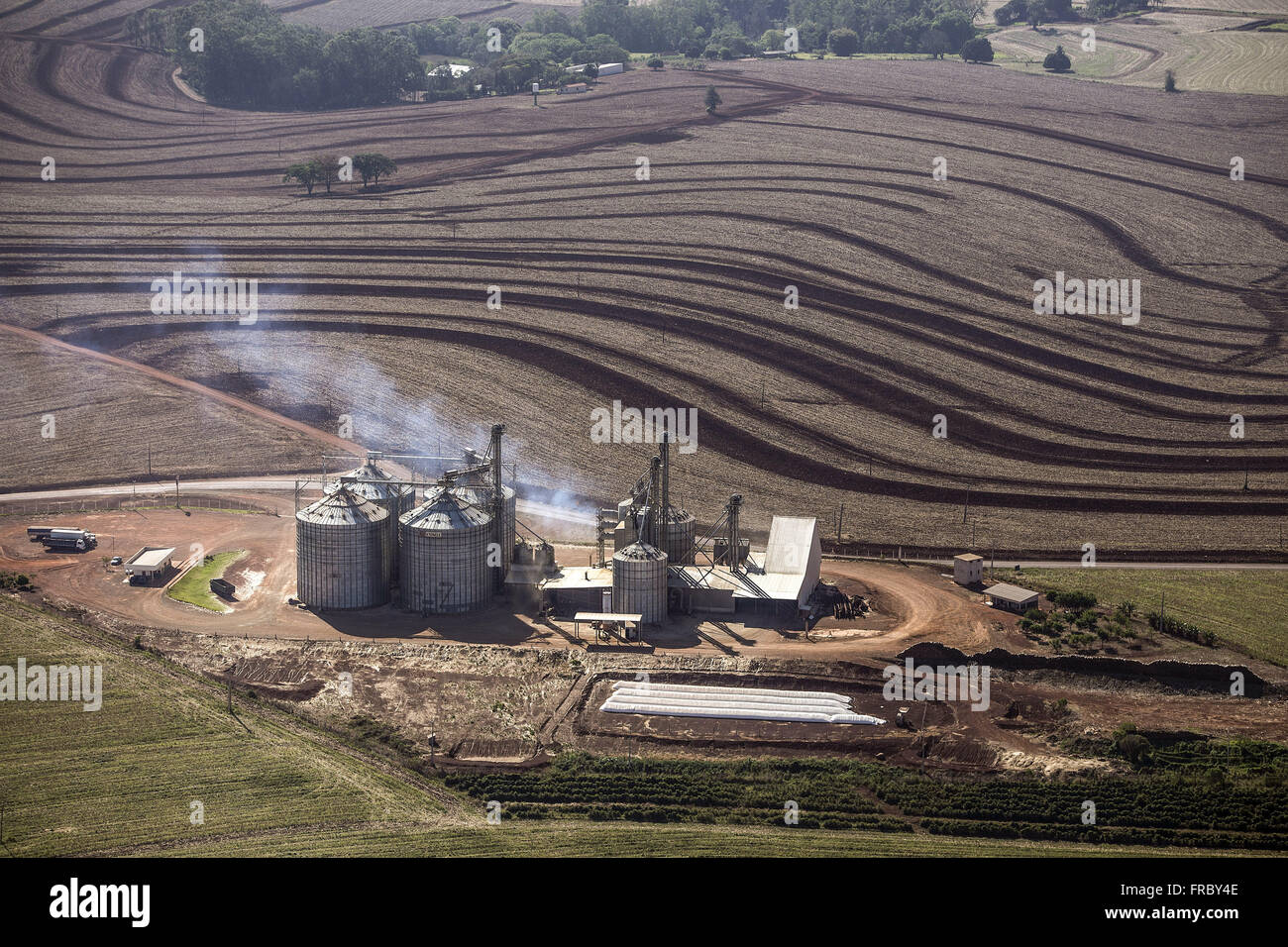 Aerial view of rural property with wheat plantation and silos - Stock Image