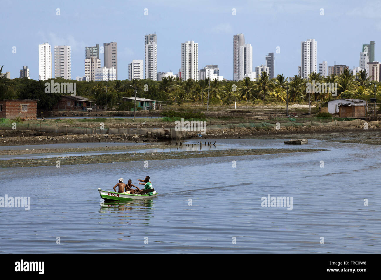 Boat on the River Island Capibaribe with God and building from Boa Viagem beach in the background Stock Photo