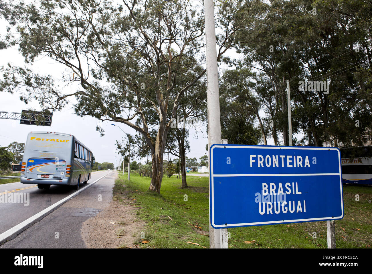 Plate indicating the border between Brazil and Uruguay in the roadside - Stock Image