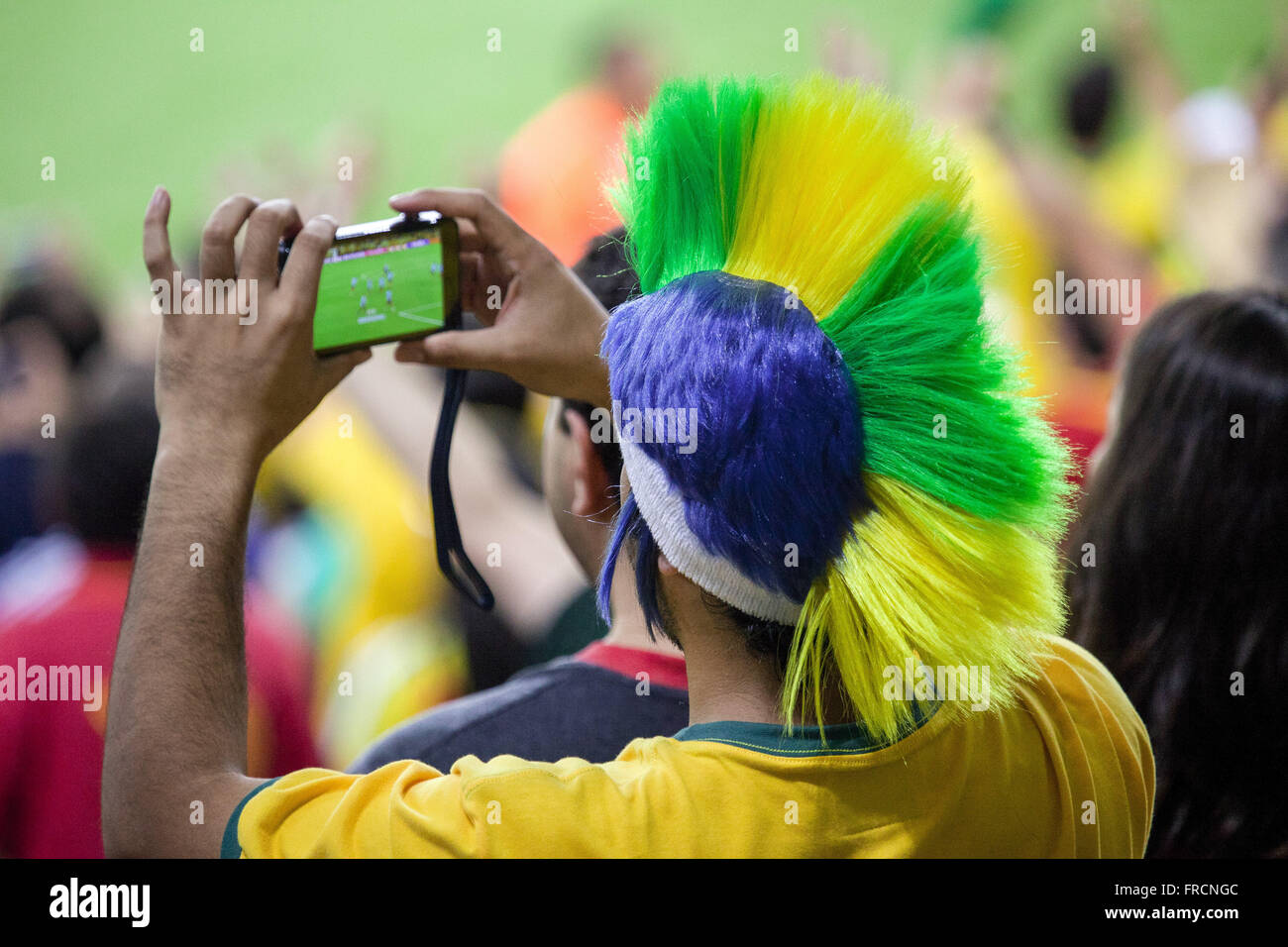Supporter photographing the match between Brazil and Spain for the final of the Confederations Cup - Stock Image