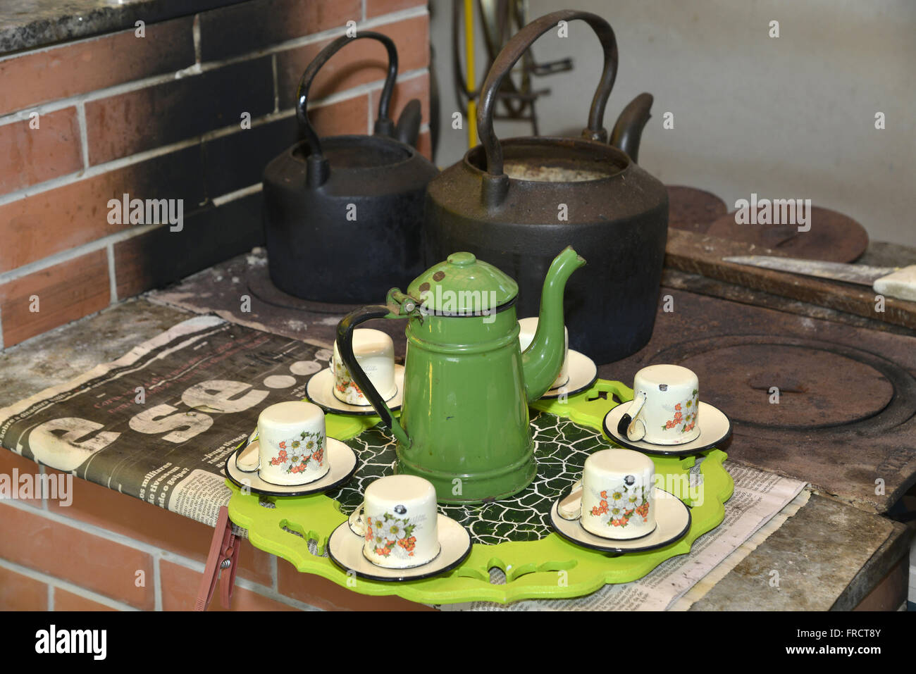 Teapot and cups of coffee on the wood stove in the countryside - Stock Image