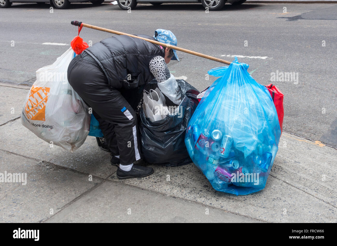 Elderly Asian woman collecting bottles and cans for the deposit in Lower Manhattan - Stock Image