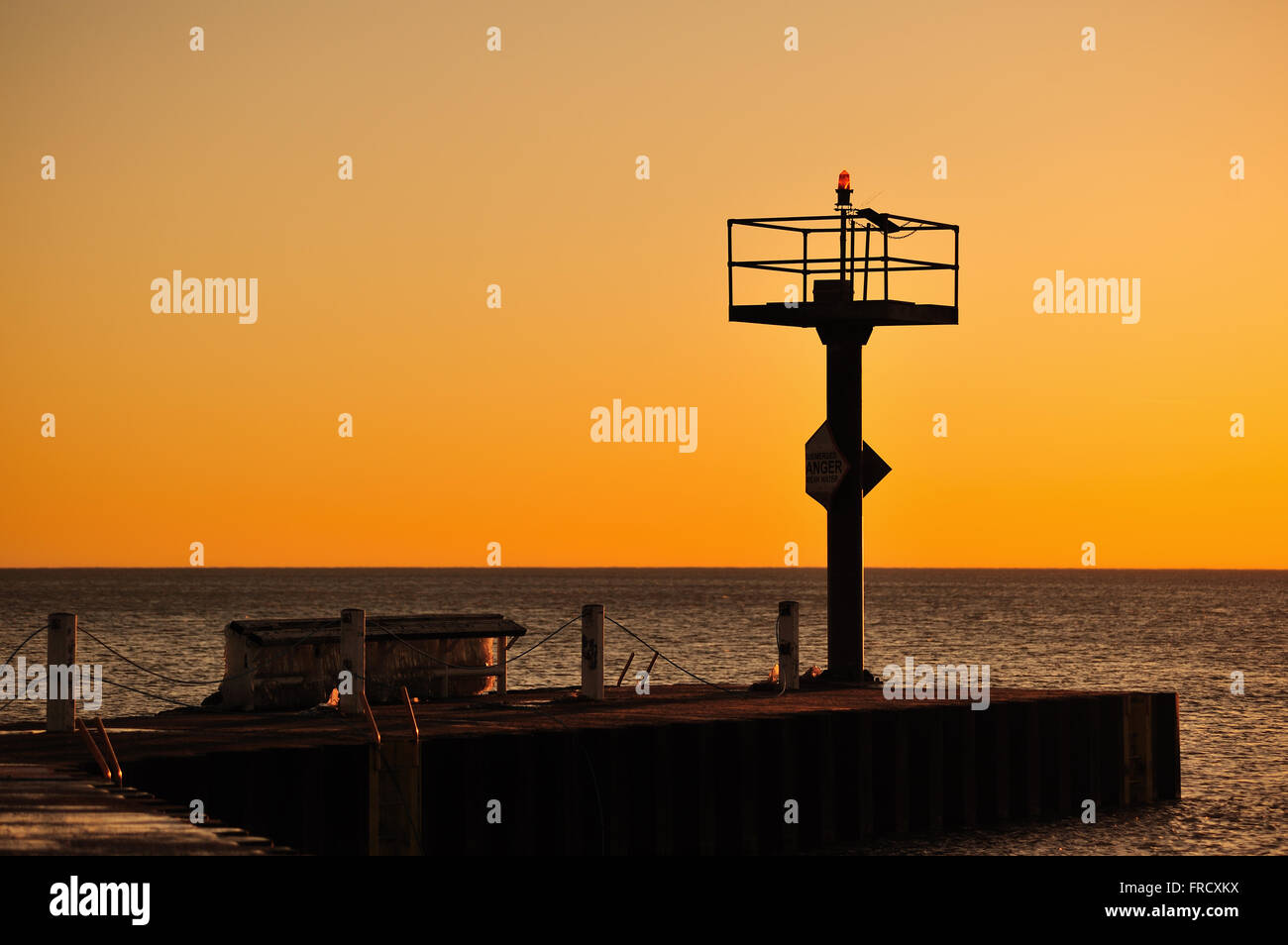 The sun rise provides strong color beyond a breakwater in Chicago's 31st Street Harbor and above Lake Michigan. - Stock Image