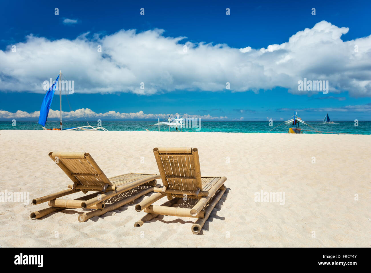 Tropical beach with chaise longues in foreground - Stock Image