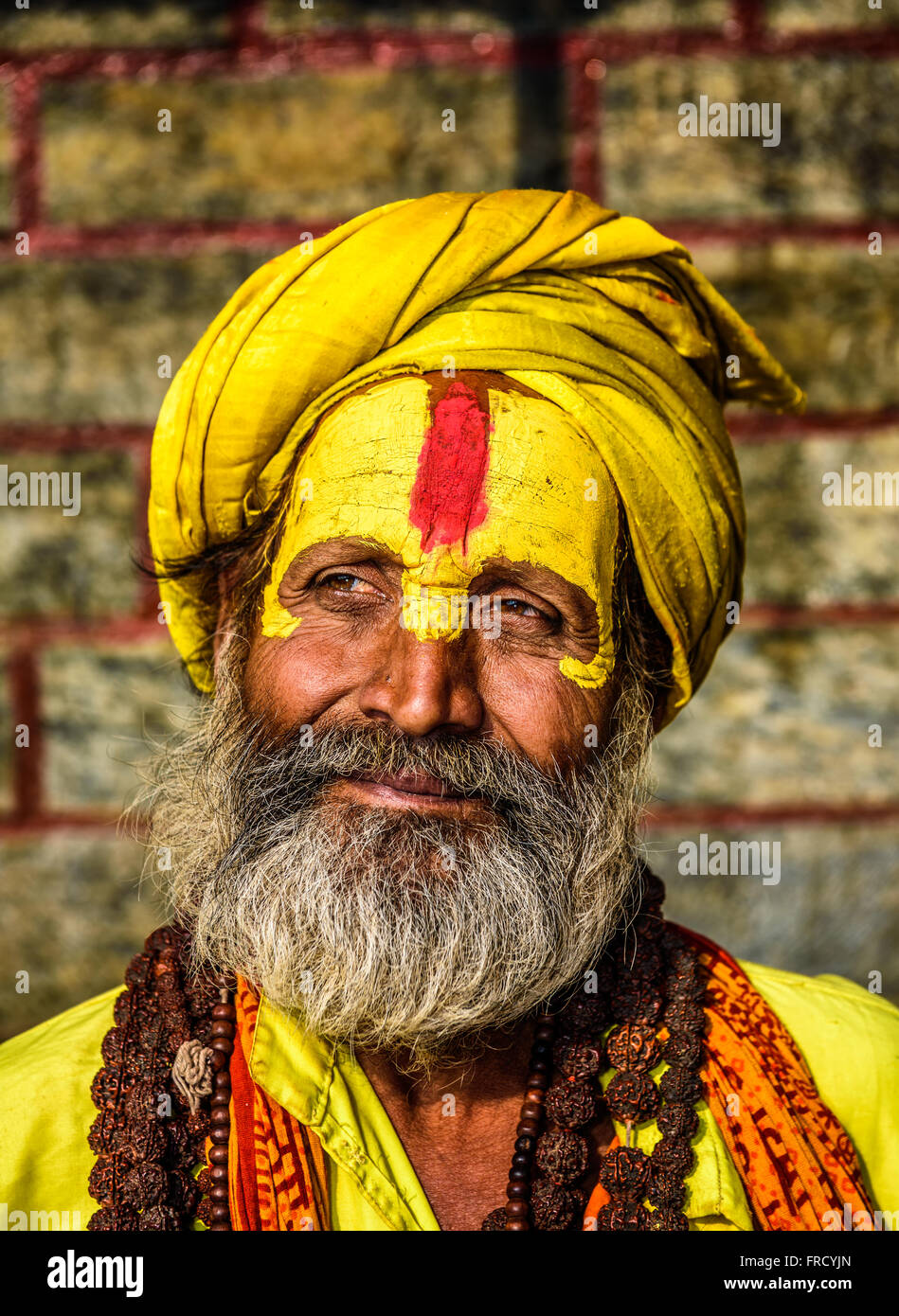 Portrait of sadhu baba (holy man) with yellow face painting in ancient Pashupatinath Temple - Stock Image
