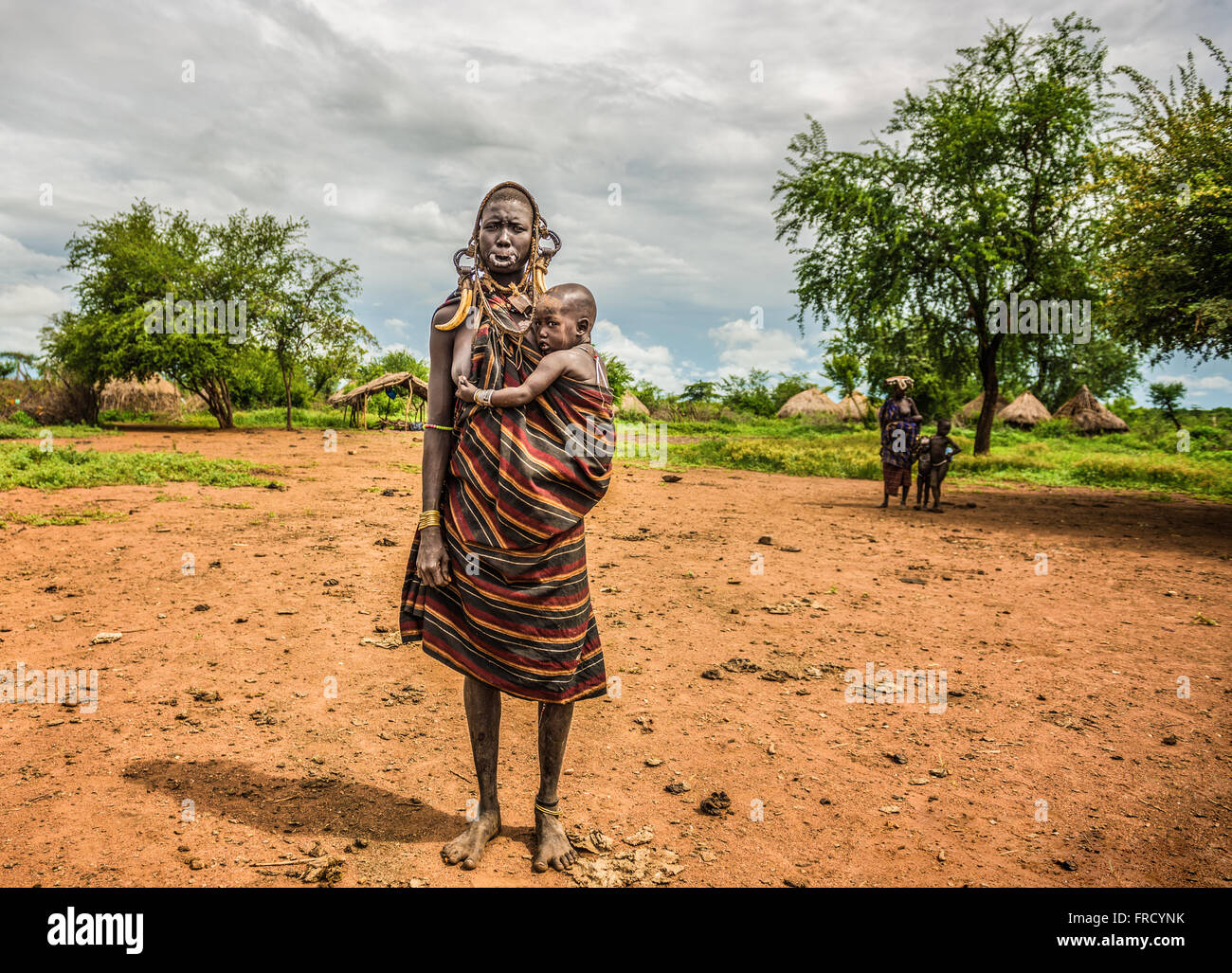 Woman from the african tribe Mursi with  her baby - Stock Image