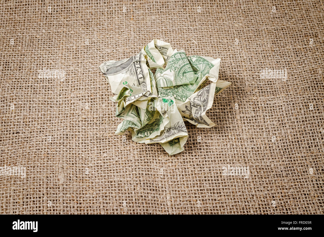 US dollar banknotes crumpled on rustic jute background - Stock Image