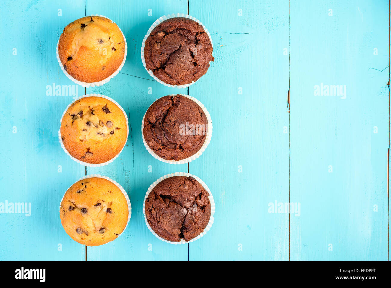 Homemade Chocolate Chip Muffins On Blue Table - Stock Image